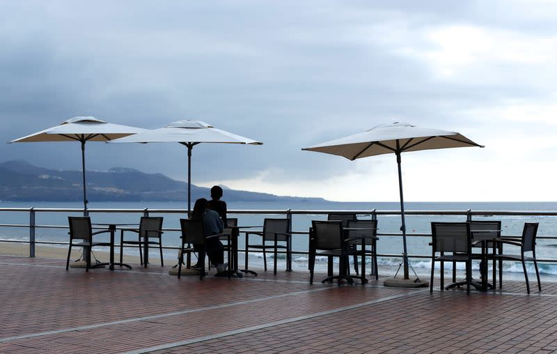People sit on a terrace at Las Canteras beach, in Gran Canaria