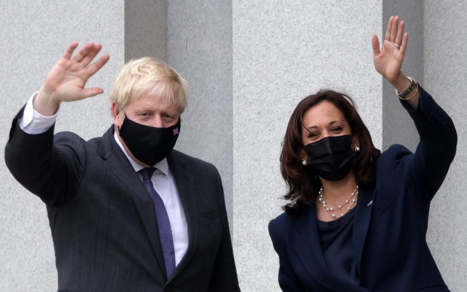 Vice President Kamala Harris and Boris Johnson wave as they tour the balcony outside the Vice President's ceremonial office at Eisenhower Executive Building - Getty