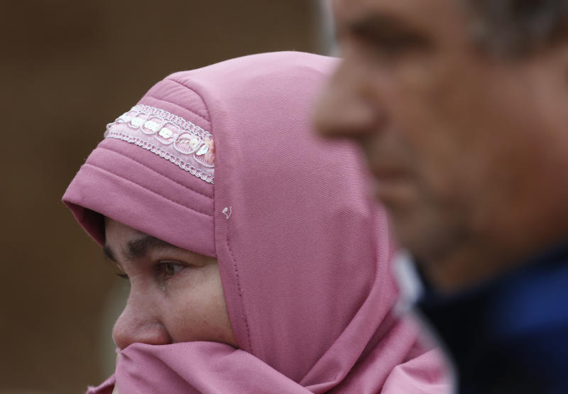 Bosnain Muslim woman Vahida Behlic, 51, cries as she searches for the remains of her mother during an exhumation at a mass grave in the village of Tomasica, near the Bosnian town of Prijedor, 260 kms north west of Sarajevo, on Thursday, Oct. 31, 2013. Forensic experts have unearthed the 360 body remains so far , but believe there are many more yet undiscovered as they excavate a 7 meters deep trench to find the remains of Bosniaks and Croats killed by Serb forces during their campaign to eliminate all non-Serbs from parts of the country they controlled during the 1992-95 Bosnian war. Authorities are still searching for 1,200 Bosniaks and Croats missing from the area of Prijedor. (AP Photo/Amel Emric)