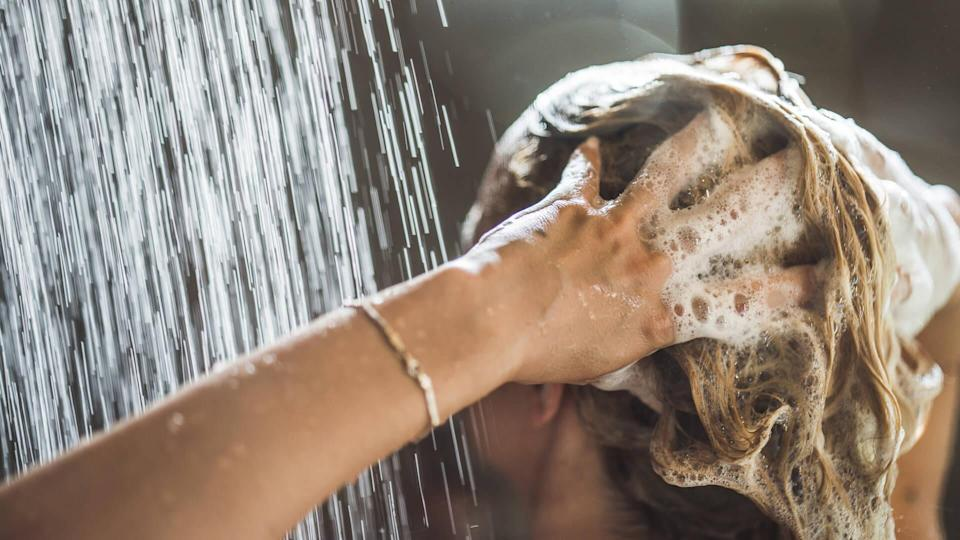 Woman washing her hair under the shower in the morning.