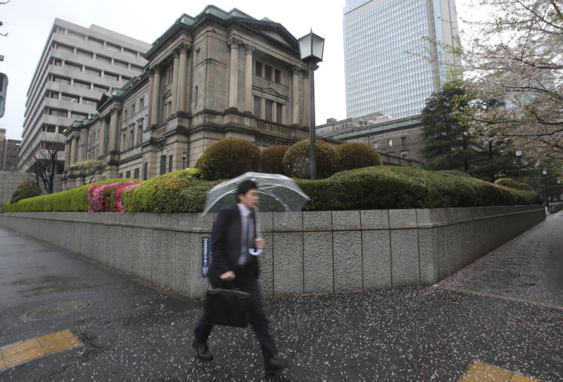 A man walks by the Bank of Japan headquarters in Tokyo Wednesday, April 3, 2013. Japan's central bank is holding its first policy meeting under a new governor amid expectations of fresh moves to ease monetary policy and spur a recovery in the world's third-largest economy. Haruhiko Kuroda took the helm at the Bank of Japan on March 19, vowing to do whatever it takes to break Japan's economy out of deflation and attain a 2 percent inflation target. (AP Photo/Shizuo Kambayashi)