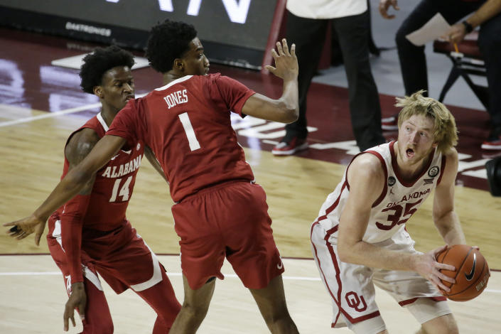 Brady Manek (35) looks to shoot against Alabama's Herbert Jones (1) and Keon Ellis (14) during the second half of an NCAA college basketball game in Norman, Okla., Saturday, Jan. 30, 2021. (AP Photo/Garett Fisbeck)