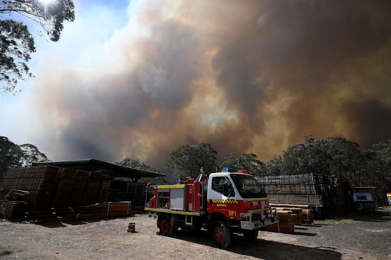 Firefighters, from Fire and Rescue NSW and NSW Rural Fire Service, help defend a property near Colo Heights. A fire truck is seen in the foreground as smoke billows above it.