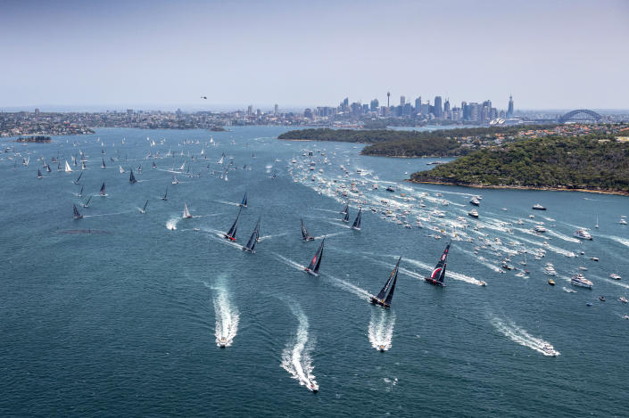 Competitors and the spectator fleet, right, race along at start of the 75th Sydney Hobart yacht race in Sydney Harbour, Thursday, Dec. 26, 2019. (Rolex/Kurt Arrigo via AP)