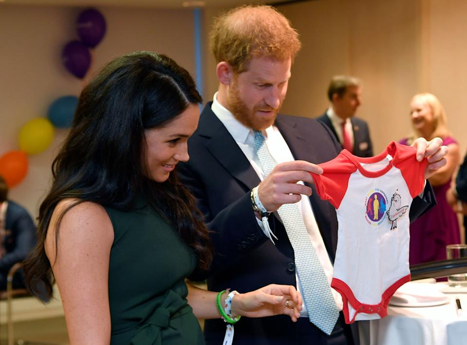 Britain's Prince Harry, Duke of Sussex, and Britain's Meghan, Duchess of Sussex view a gift for their son Archie as they attend the annual WellChild Awards in London on October 15, 2019. - WellChild is the national charity for seriously ill children and their families. The WellChild Awards celebrate the inspiring qualities of some of the country's seriously ill young people and the dedication of those who care for and support them. (Photo by TOBY MELVILLE / POOL / AFP) (Photo by TOBY MELVILLE/POOL/AFP via Getty Images)