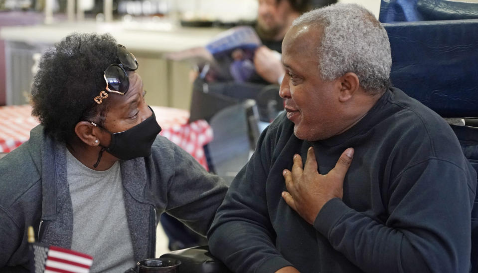 """Craig Rawls, an Army National Guardsman, right, speaks with his wife Chris Rawls, with only a face mask as a protective garment at the Mississippi State Veterans Home in Collins, Miss., as part of Operation """"Family Reunion,"""" Thursday, April 1, 2021. Due to the relaxation of protocols designed to slow the spread of coronavirus, the veterans home allowed indoor, in-person visits between veterans and two family members without the use of PPE for the first time since March of 2020. (AP Photo/Rogelio V. Solis)"""