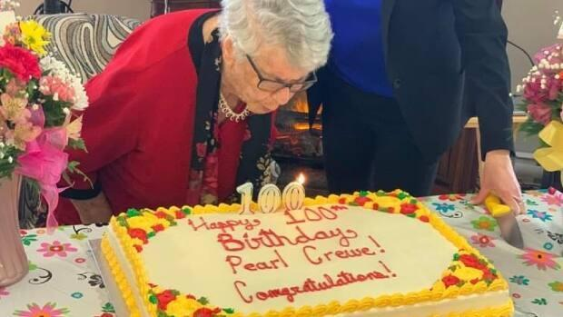 Pearl Crewe makes a wish and blows out the candles on her 100th birthday cake. (Angela Dearing - image credit)