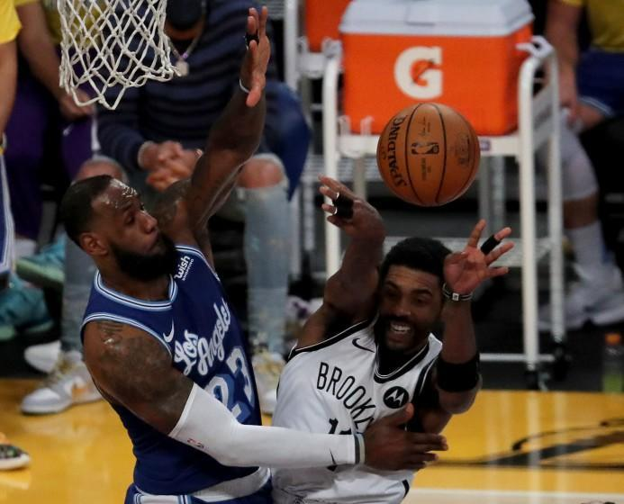 Lakers forward LeBron James defends against Nets guard Kyrie irving