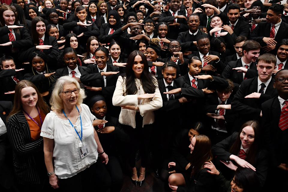 LONDON, ENGLAND - MARCH 06: Meghan, Duchess of Sussex poses with school children making the 'Equality' sign following a school assembly during a visit to Robert Clack School in Dagenham to attend a special assembly ahead of International Women's Day (IWD) held on Sunday 8th March, on March 6, 2020 in London, England.   (Photo by Ben Stansall-WPA Pool/Getty Images)