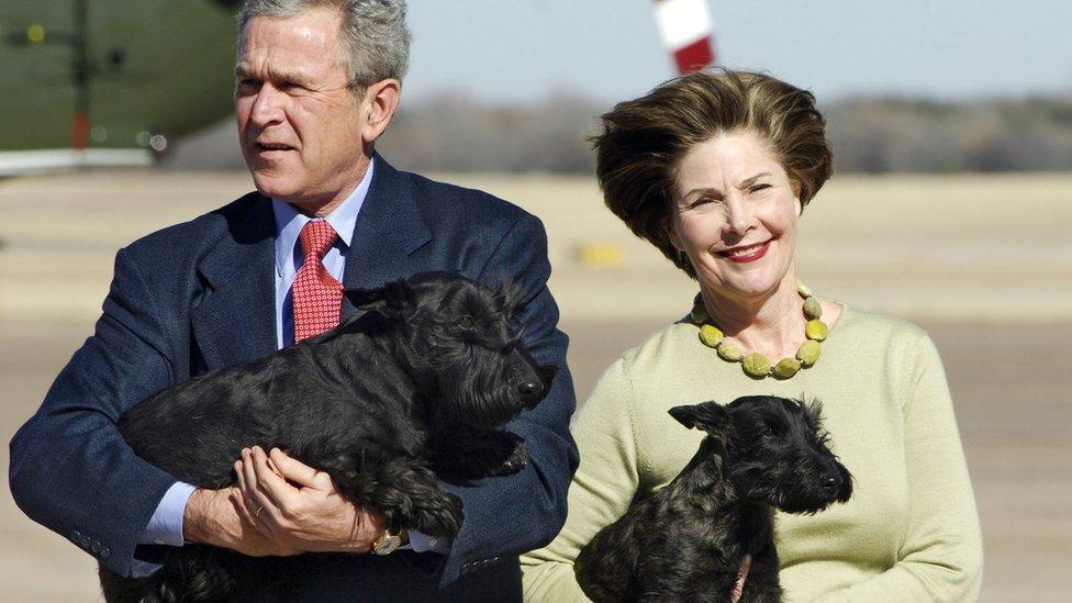 US President George W. Bush carries his dog Barney as Fist Lady Laura Bush holds Miss Beazley in 2005