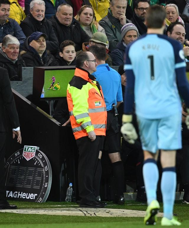 Paul Tierney consulted the pitchside monitor before changing Norwich City's Ben Godfrey's card from a yellow to a red
