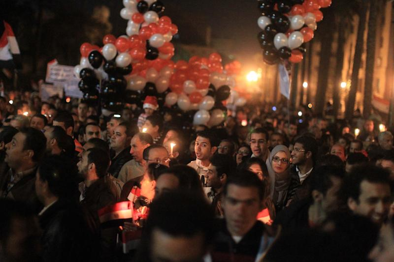 <strong>Thousands of Egyptian Muslims and Coptic Christians attend a celebration on New Year's eve in Tahrir Square in Cairo, on December 31, 2011.</strong> (Photo: KHALED DESOUKI via Getty Images)