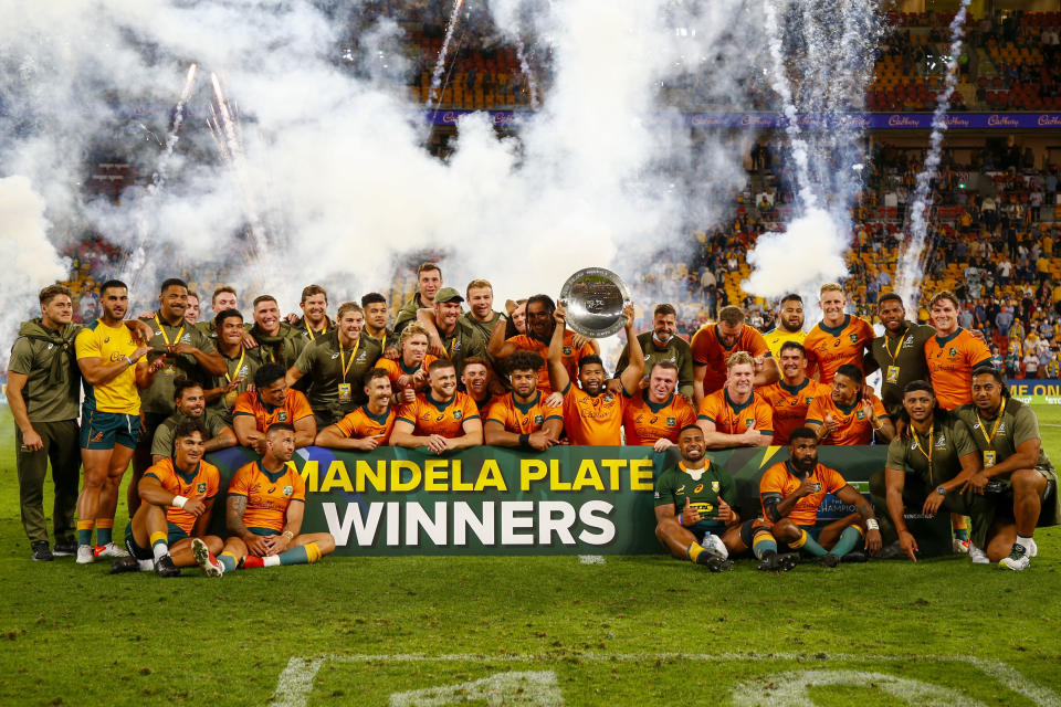 The Australian team celebrate after defeating South Africa to win the Nelson Mandela Plate during the Rugby Championship test match between the Springboks and the Wallabies in Brisbane, Australia, Saturday, Sept. 18, 2021. (AP Photo/Tertius Pickard)