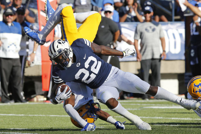 McNeese State defensive back Trent Jackson, rear, flips as he attempts to tackle BYU running back Squally Canada (22) in the first half during an NCAA college football game Saturday, Sept. 22, 2018, in Provo, Utah. (AP Photo/Rick Bowmer)
