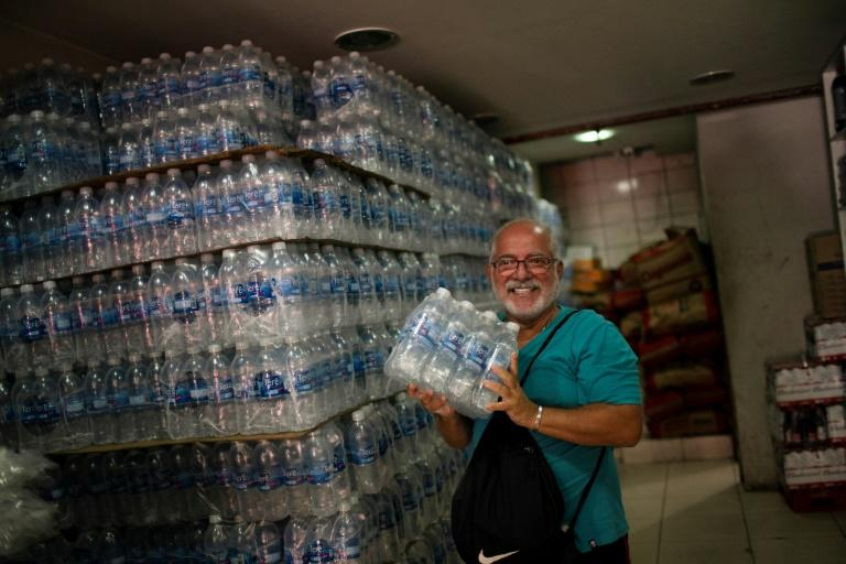 A man smiles after finding bottled water on sale in a liquor store in  Rio de Janeiro on January 15, 2020