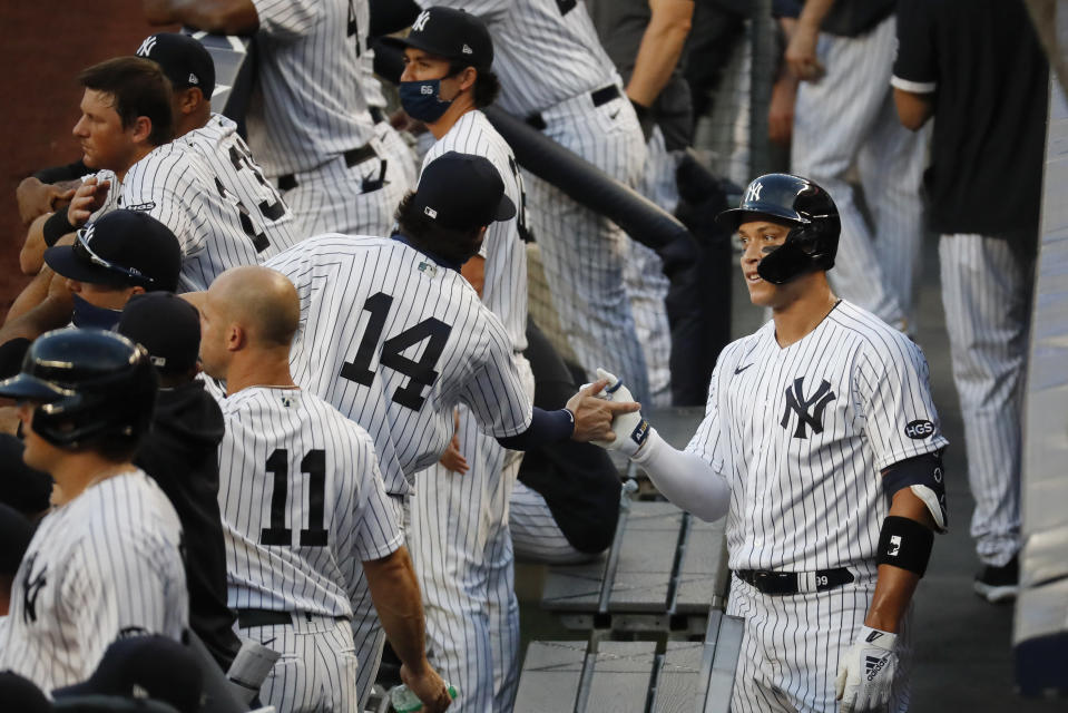 New York Yankees' Aaron Judge, right, celebrates with Tyler Wade (14) in the dugout after hitting a solo home run off Boston Red Sox starting pitcher Zack Godley during the first inning of a baseball game Saturday, Aug. 1, 2020, in New York. (AP Photo/John Minchillo)