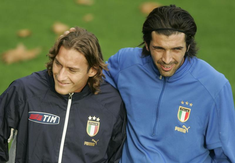 Italy's national soccer team's goalie Gianluigi Buffon, right, pats on the head teammate Francesco Totti on the head, during a training session in Coverciano, near Florence, central Italy, Sunday, Oct. 10, 2004. Italy, after being defeated 1-0 by Slovenia Saturday, Oct. 9, is scheduled to play Belarus next Wednesday, Oct. 13 in a World Cup group 8 qualifying match. (AP Photo/Fabrizio Giovannozzi)