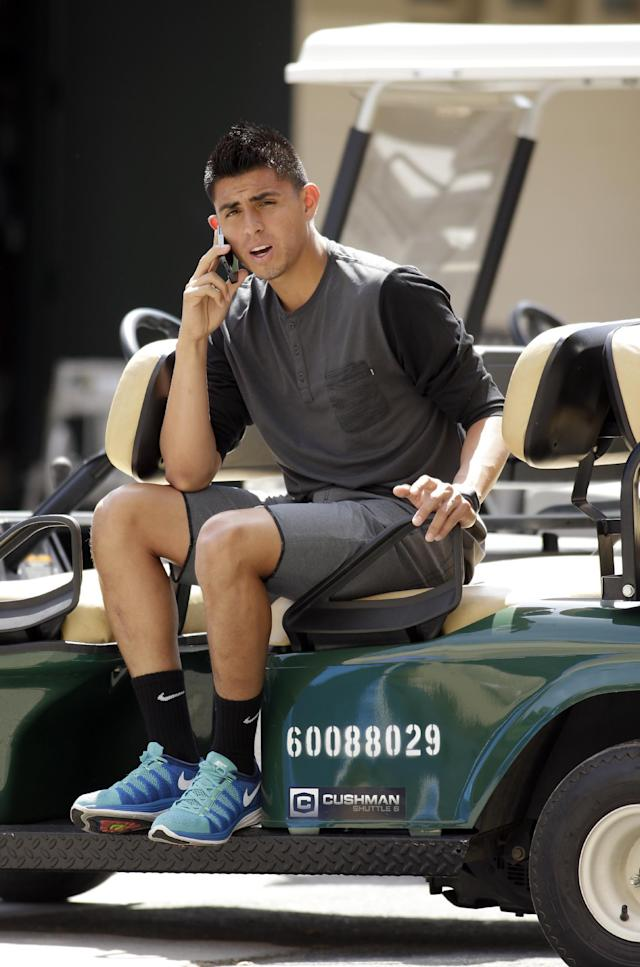 United States' Joe Corona of Mexico makes a phone call from a golf cart prior to practice in preparation for the World Cup soccer tournament on Thursday, May 22, 2014, in Stanford, Calif. (AP Photo/Ben Margot)
