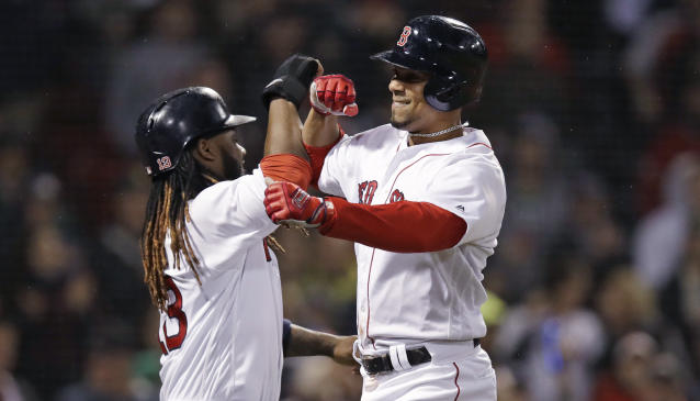 Boston Red Sox's Xander Bogaerts, right, is congratulated by Hanley Ramirez after crossing home plate on his three-run home run off Oakland Athletics relief pitcher Ryan Dull during the sixth inning of a baseball game at Fenway Park in Boston, Wednesday, May 16, 2018. (AP Photo/Charles Krupa)