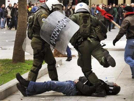 A riot policeman kicks an anti-austerity protester who fell during clashes in Athens' Syntagma (Constitution) square, February 10, 2012.