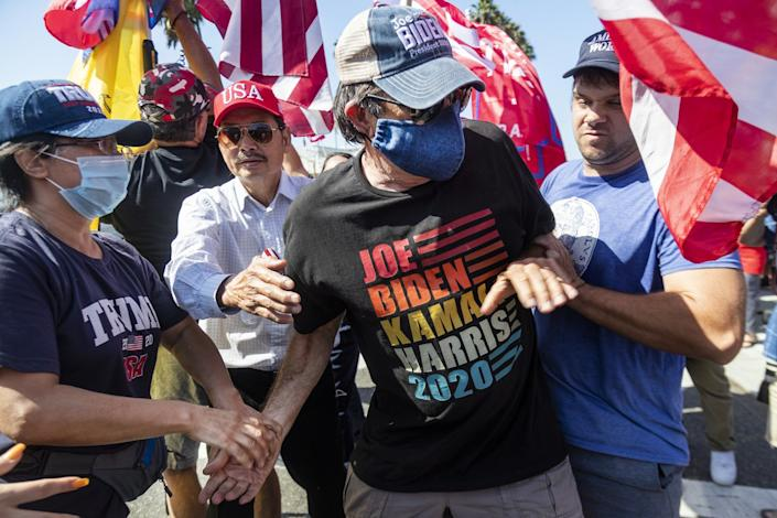 Biden supporter Richard Williams is grabbed and shoved by Trump supporters