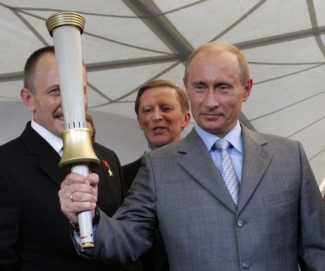 FILE - In this Aug. 11, 2007 file photo, Russian President Vladimir Putin holds one of the torches produced for the 1980 Moscow Olympics during a visit to the Klimov Aircraft Engines Corporation, which made the torches, in St. Petersburg, Russia. Thirty-four years after those Olympics, Putin has similar ambitions: Proving to the world through the 2014 Sochi games that post-Soviet Russia remains a global player, if no longer a superpower. (AP Photo/Alexander Zemlianichenko, File)