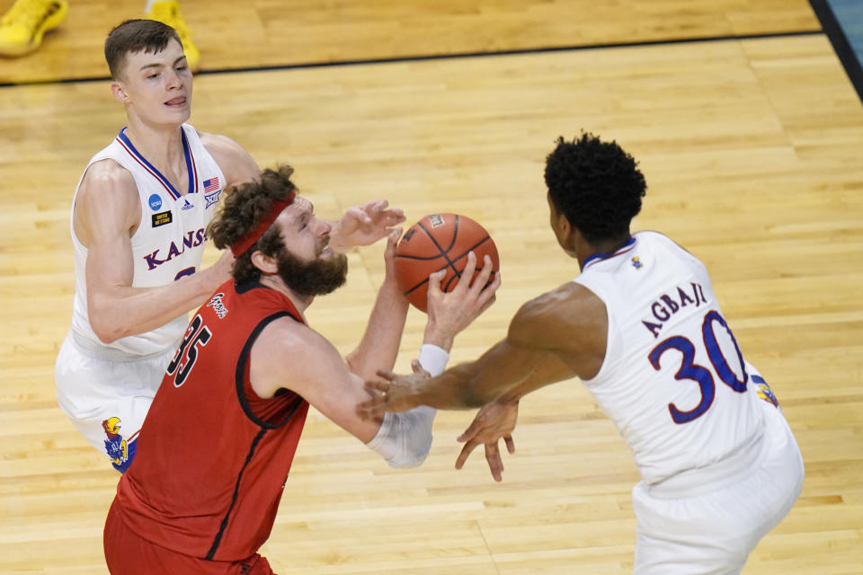 Eastern Washington forward Tanner Groves (35) is pressured by Kansas guard Christian Braun, left, and Kansas guard Ochai Agbaji (30) as he goes up for a shot during the second half of a first-round game in the NCAA college basketball tournament at Farmers Coliseum in Indianapolis, Saturday, March 20, 2021. (AP Photo/AJ Mast)