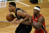 Milwaukee Bucks' Giannis Antetokounmpo drives past New Orleans Pelicans' Eric Bledsoe during the second half of an NBA basketball game Thursday, Feb. 25, 2021, in Milwaukee. (AP Photo/Morry Gash)