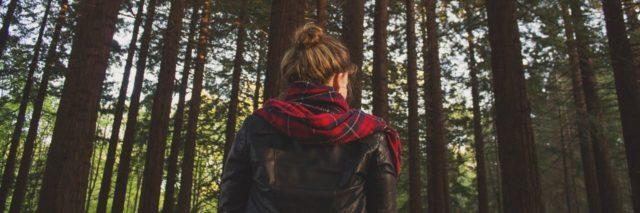 photo of young woman with blonde hair from behind in woods with tall trees