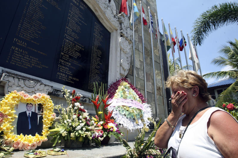 Australian Carmen Cacha, who lost her son in the 2002 Bali bombings, looks at her son's photograph while paying her respects at the Bali Memorial Monument in Kuta, Bali, Indonesia on Thursday, Oct. 11, 2012. Australian Prime Minister Julia Gillard is scheduled to attend Friday's event remembering the Oct. 12, 2002, attacks that blasted two Bali nightclubs. The bombs killed 202 people, including 88 Australians and seven Americans.  (AP Photo/Firdia Lisnawati)