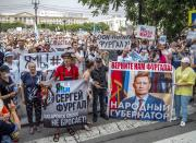 """People hold posters reading """"Freedom for Sergei Furgal, I am, we are Sergei Furgal,"""" """"Give us Furgal back"""", """"Call Furgal home"""" during an unsanctioned protest in support of Sergei Furgal, the governor of the Khabarovsk region, in Khabarovsk, 6100 kilometers (3800 miles) east of Moscow, Russia, Saturday, July 18, 2020. Tens of thousands of people in the Russian Far East city of Khabarovsk took to the streets on Saturday, protesting the arrest of the region's governor on charges of involvement in multiple murders. Local media estimated the rally in the city attracted from 15,000 to 50,000 people. (AP Photo/Igor Volkov)"""