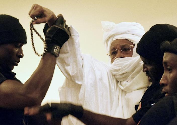 Former Chadian dictator Hissene Habre C) is escorted by prison guards ahead of a 2015 court appearance in Dakar (AFP Photo/Seyllou)