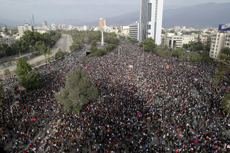 Demonstrators protest against the government in Santiago, Chile, Monday, Nov. 4, 2019. Chile has been facing weeks of unrest, triggered by a relatively minor increase in subway fares. The protests have shaken a nation noted for economic stability over the past decades, which has seen steadily declining poverty despite persistent high rates of inequality. (AP Photo/Esteban Felix)
