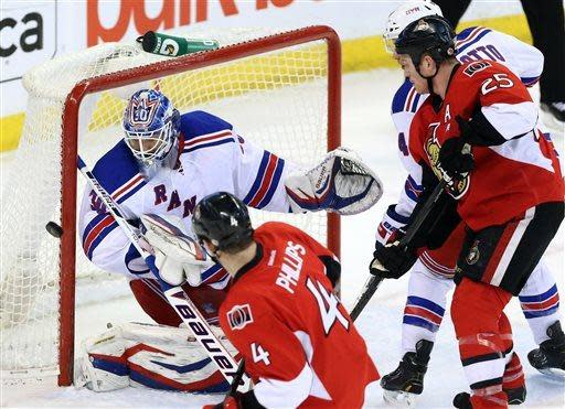 New York Rangers goaltender Henrik Lundqvist covers the post as Ottawa Senators' Chris Phillips (4), Chris Neil (25) and Rangers' Michael Del Zotto watch during the first period of their NHL hockey game, Thursday, March 28, 2013, in Ottawa, Ontario. (AP Photo/The Canadian Press, Fred Chartrand)
