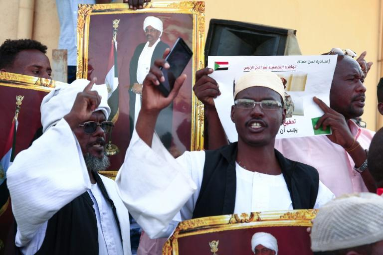 Supporters of Sudan's ousted president Omar al-Bashir hold images of him as they demonstrate in front of a court in the capital Khartoum (AFP Photo/Ebrahim HAMID)
