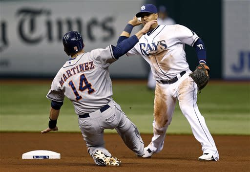 Tampa Bay Rays shortstop Yunel Escobar throws over Houston Astros' J.D. Martinez to complete a double play on batter Carlos Corporan during the fourth inning of a baseball game, Friday, July 12, 2013, in St. Petersburg, Fla. (AP Photo/Mike Carlson)