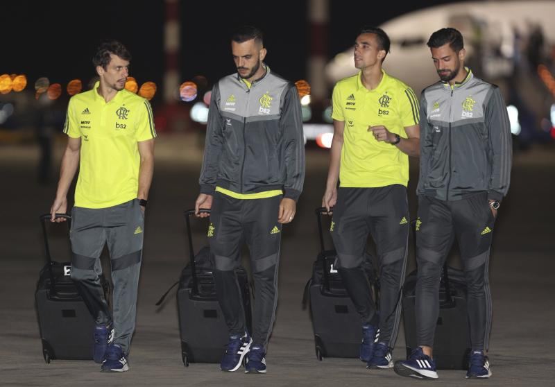 Rodrigo Caio, left, Rhodolfo, second left, Cesar, second right and Pablo Mari of Brazil's Flamengo soccer team walk on the airport tarmac after arriving to the military airport Grupo Aereo 8, in Lima, Peru, Wednesday, Nov. 20, 2019. The team will play Argentina's River Plate on Saturday's Copa Libertadores final. (AP Photo/Martin Mejia)