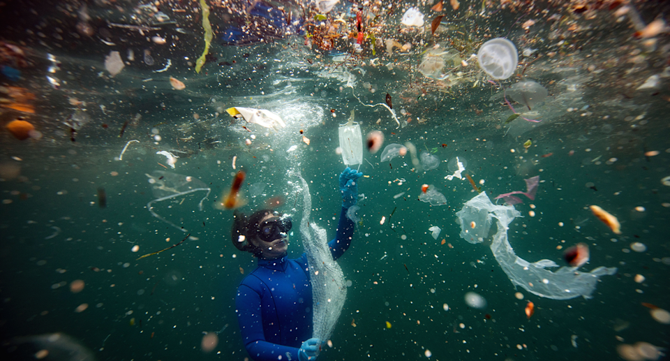 Diver looks at pieces of plastic floating in the ocean. Source: Getty Images