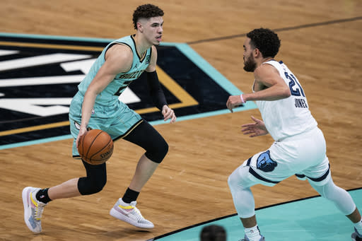 Charlotte Hornets guard LaMelo Ball (2) is defended by Memphis Grizzlies guard Tyus Jones (21) during the first half of an NBA basketball game in Charlotte, N.C., Friday, Jan. 1, 2021. (AP Photo/Jacob Kupferman)