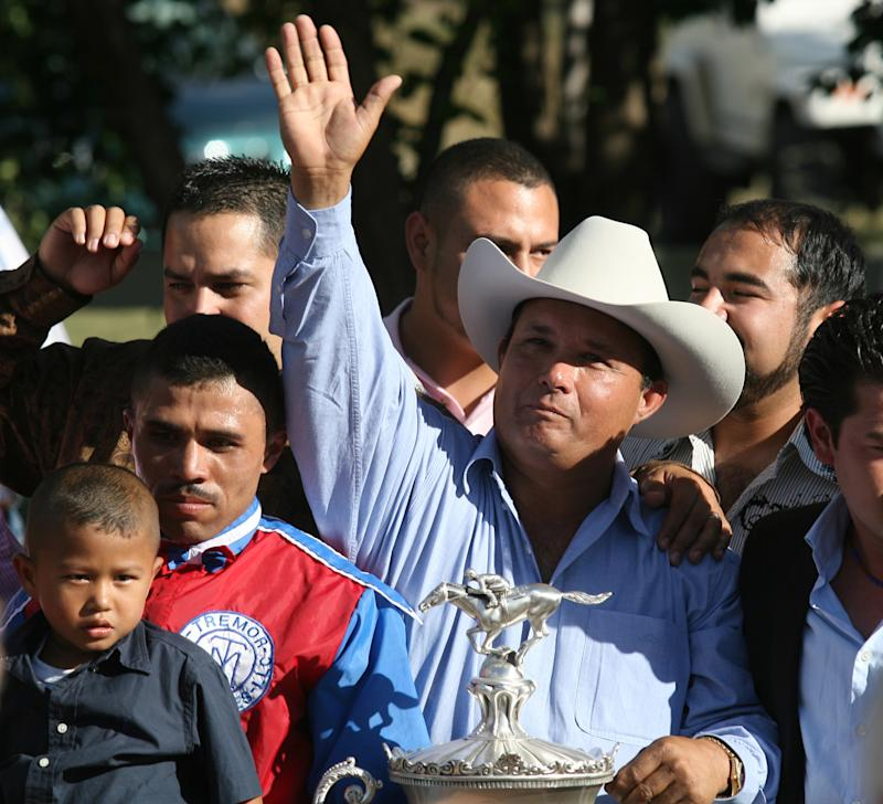 In this photo taken Sept. 6, 2010, owner Jose Trevino Morales, center, acknowledges the crowd as he stood with the trophy after Mr. Piloto won the All American Futurity horse race at Ruidoso Downs, N.M. Federal agents raided a sprawling ranch in Oklahoma and the prominent quarter horse track in New Mexico on Tuesday, June 12, 2012, alleging the brother of a high-ranking official in a Mexican drug cartel used a horse-breeding operation to launder money.  Seven of the 14 people indicted were arrested, including Jose Trevino Morales.  (AP Photo/The El Paso Times, Rudy Gutierrez)  EL DIARIO OUT; JUAREZ MEXICO OUT;