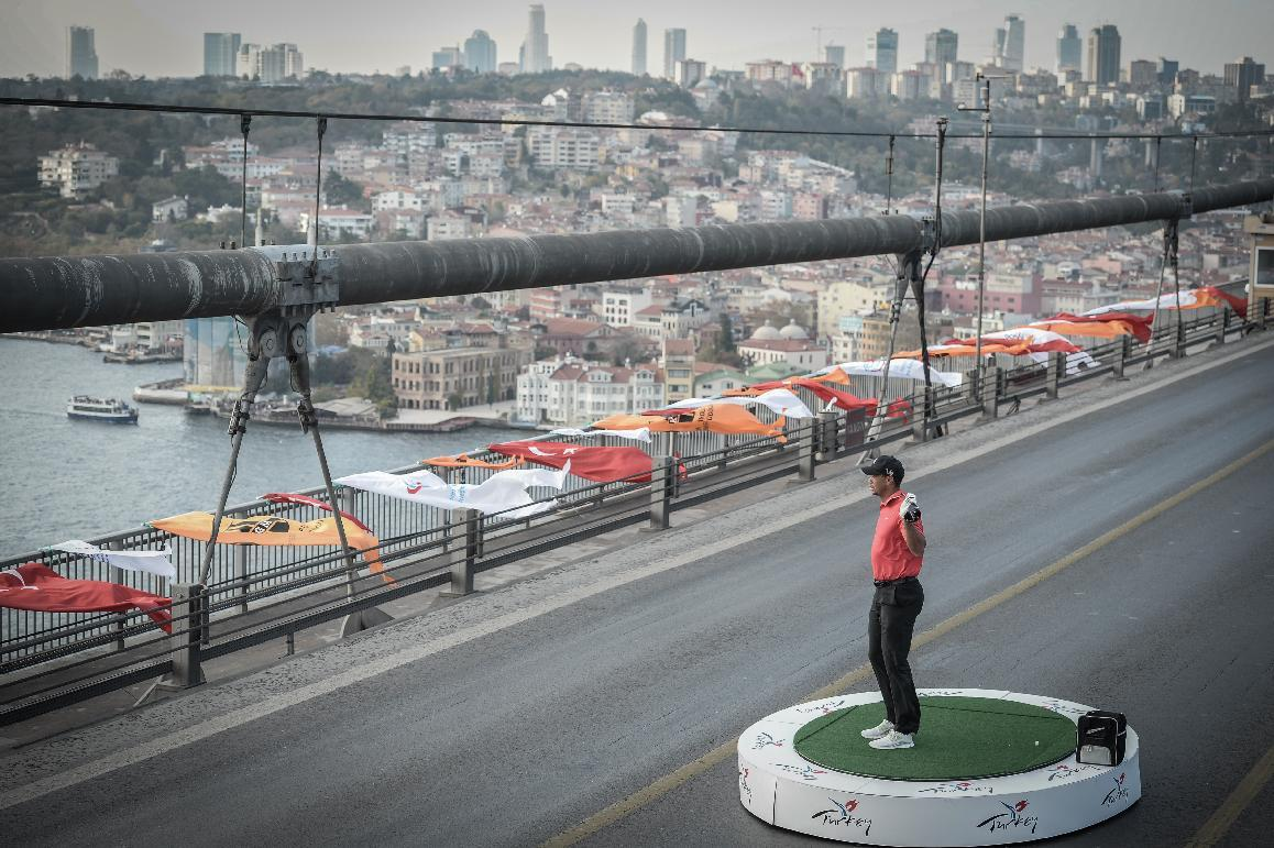 Golf star Tiger Woods of the United States poses for photographers after his shot from East to West on the iconic Bosporus Bridge that separates the continents of Europe and Asia, in Istanbul, Turkey, Tuesday, Nov. 7, 2013. Woods will compete in the USD7million Turkish Airlines Open in Antalya, Nov. 7-10. (AP Photo)
