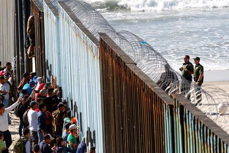 Migrants look through the border fence between Mexico and the United States in Tijuana