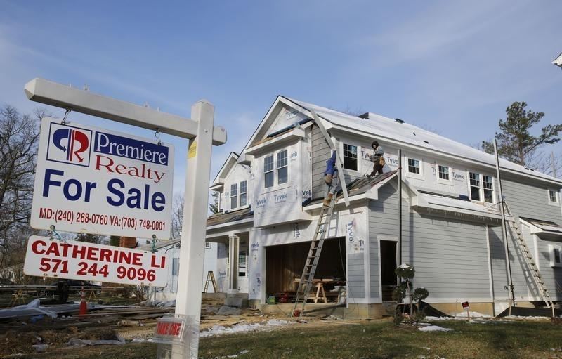 New home is being built next to a home with a for sale sign on a street in Vienna, on the morning the National Association of Realtors issues its Pending Home Sales for February report, in Virginia