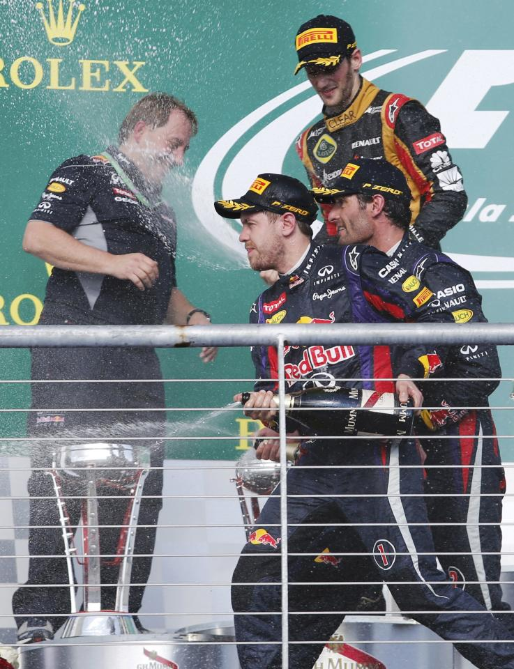 Red Bull Formula One driver Sebastian Vettel (front) of Germany, teammate Mark Webber of Australia (R) and Lotus Formula One driver Romain Grosjean of France (top R) spray champagne next to Red Bull Racing's Head of IT Matt Cadieux during celebrations on the podium after the Austin F1 Grand Prix at the Circuit of the Americas in Austin November 17, 2013. REUTERS/Adrees Latif (UNITED STATES - Tags: SPORT MOTORSPORT F1)