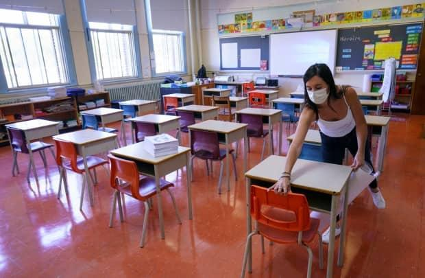 A teacher in Montreal arranges desks in late August. With the new school year now underway, the debate over the safety of large class sizes has returned amid the ongoing COVID-19 pandemic. (Paul Chiasson/The Canadian Press - image credit)