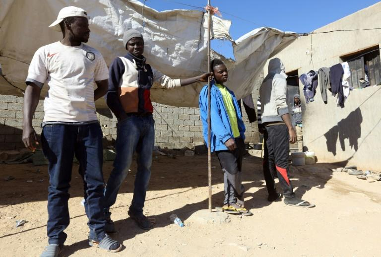 African migrants stand under the sun at a shelter in the town of Bani Walid, on the edge of the desert southeast of the Libyan capital Tripoli