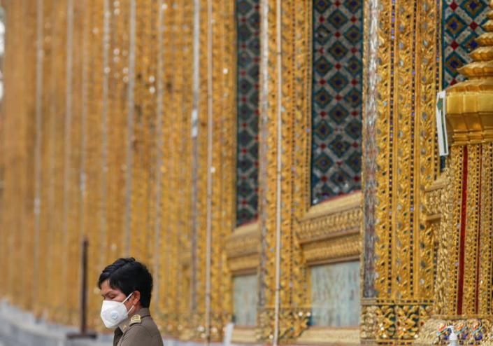 A police officer wears a protective face mask at Emerald Buddha temple, amid fear of coronavirus in Bangkok