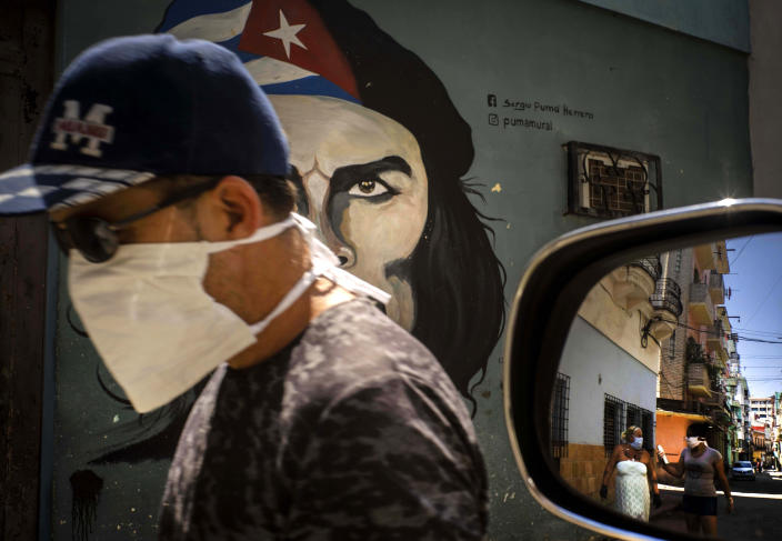 """A man wearing a mask walks alongside a mural of Ernesto """"Che"""" Guevara as other pedestrians are reflected in the side-view mirror of a car in Havana, Cuba, Tuesday, April 7, 2020. Cuban authorities are requiring people use masks outside their homes as a measure to help contain the spread of the new coronavirus. (AP Photo/Ramon Espinosa)"""