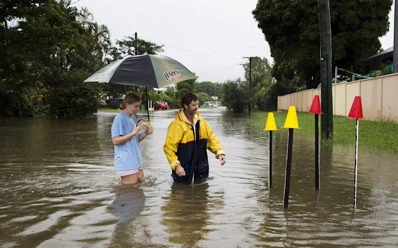 Local resident Paul Shafer and his daughter Lily stand in floodwaters near star pickets that show where the storm water cover has been removed in Hermit Park, Townsville - REUTERS