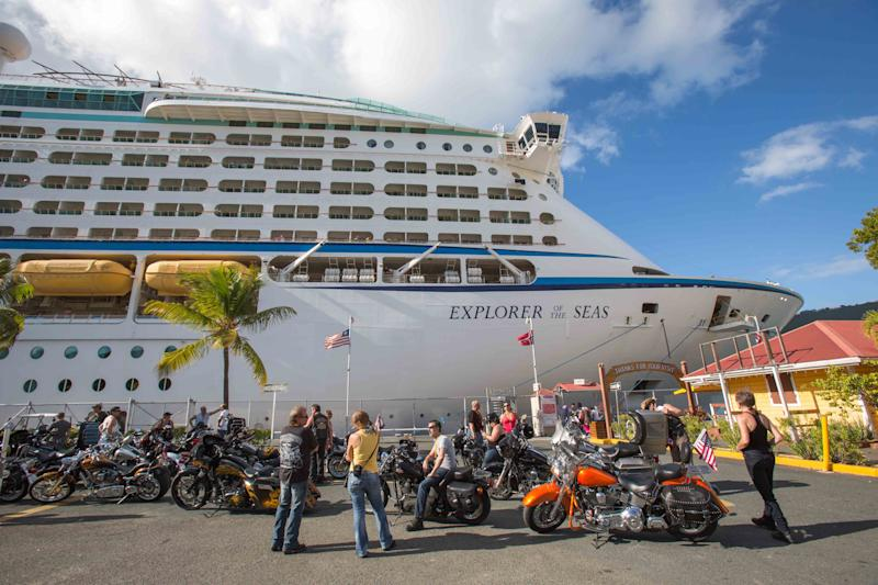 Passengers from a motorcycle cruises' tour group, prepare to board the Royal Caribbean International's Explorer of the Seas, docked at Charlotte Amalie Harbor in St. Thomas, U. S. Virgin Islands, Sunday, Jan. 26, 2014. Health officials have boarded the cruise liner to investigate an illness outbreak that has stricken at least 300 people with gastrointestinal symptoms including vomiting and diarrhea. Over 13 of the 34 motorcycle riders fell ill during the trip. (AP Photo/Thomas Layer)